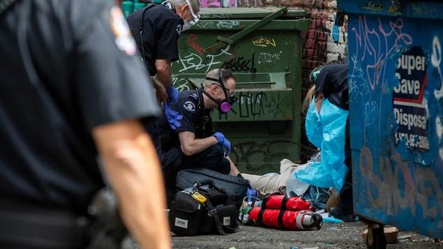 Des ambulanciers aident une personne allongée au sol dans une ruelle.