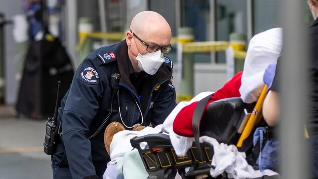 Un ambulancier pousse une civière.