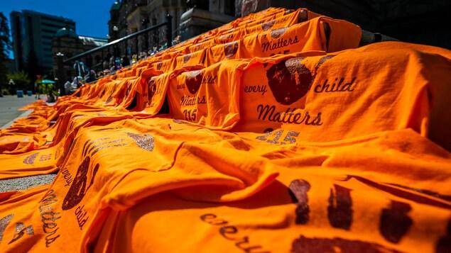 Nasa hagdan sa tapat ng building ang mga orange na t-shirt na nagsasabing every child matters.