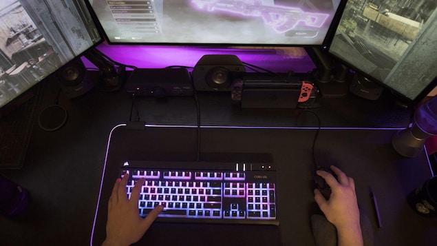 Des mains posées sur un clavier et un souris devant un ordinateur.