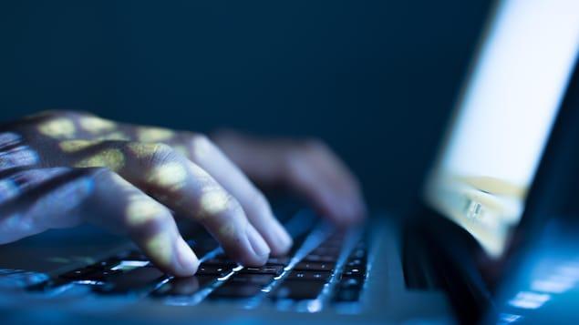Une personne tape sur un clavier d'ordinateur portable.