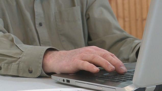 Un homme utilise un ordinateur.