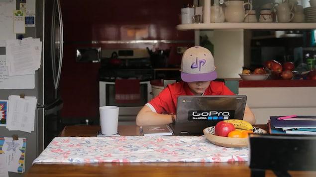 Un garçon utilise un ordinateur portable sur une table de cuisine.