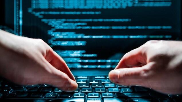 Des mains en train de taper sur le clavier d'un ordinateur portable qui affiche une série de codes.