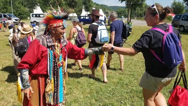 Poignée de main entre une jeune fille et un Autochtone