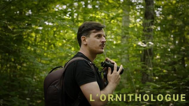 L'ornithologue Olivier Barden se promène dans la forêt, jumelles à la main.