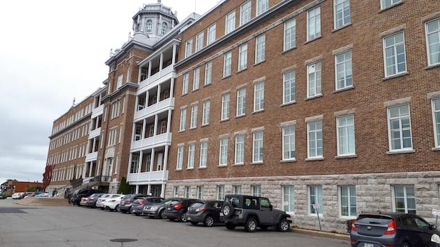Façade de l'actuel Centre jeunesse de Québec. Le revêtement extérieur est fait de pierres grises et de briques marron. On aperçoit des voitures stationnées devant l'édifice.