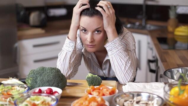 Une femme n'arrive pas à choisir entre des assiettes de légumes