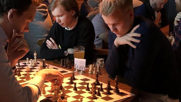 Des joueurs sont concentrés devant des jeux d'échecs.
