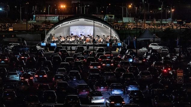 Des voitures sont devant une scène sur laquelle jouent les membres de l'OSM.