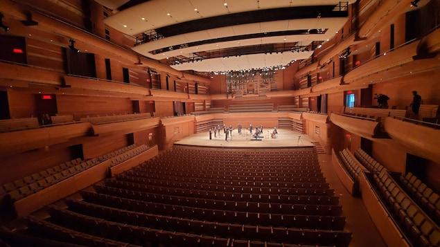 Salle de concert vide avec une dizaine de musiciens sur scène, vus de loin.