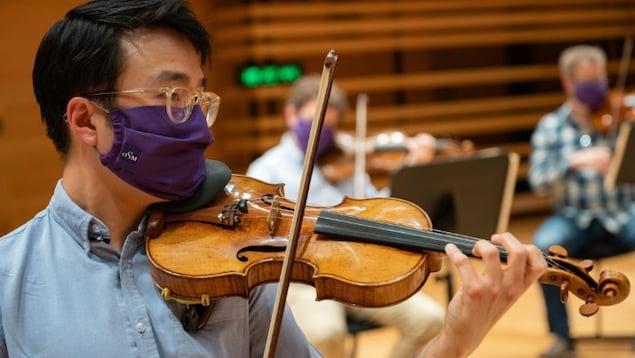 Trois musiciens jouent de leur instrument en portant un masque hygiénique.