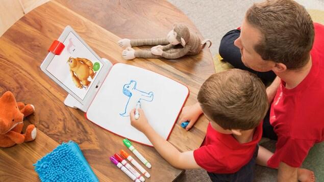 Un enfant dessine assisté d'un monstre virtuel qui le guide dans sa tâche.