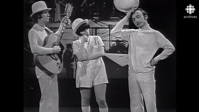Les trois artistes gesticulent. Robert Charlebois joue de la guitare.