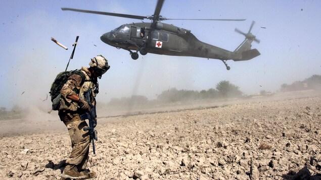 Un soldat canadien de l'OTAN attend l'hélicoptère qui est en train d'atterrir.