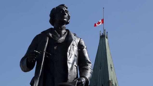 Le drapeau canadien est en berne au-dessus de la tour de la Paix, près d'une statue, sur la colline du Parlement à Ottawa.