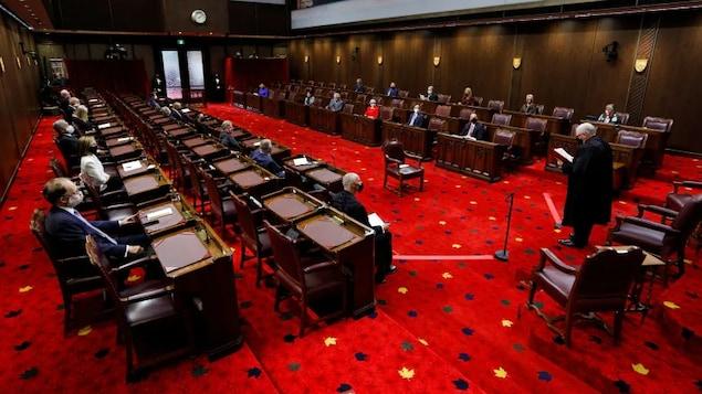 Des sénateurs masqués sont assis à leur bureau dans la Chambre haute.