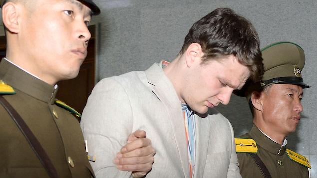 Un jeune homme la tête baissée, entre deux policiers nord-coréens