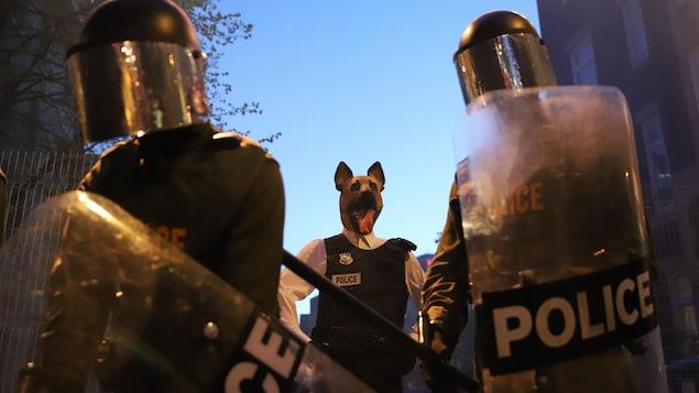 Des personnages de La souricière. On voit des policiers et un chien vêtu d'un costume de policier.