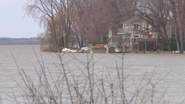 De l'eau se rapproche d'une maison située aux abords de la rivière des Outaouais.