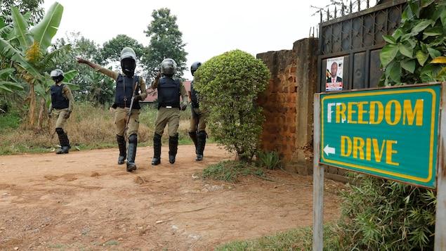 Des policiers gardent une route menant à la résidence de l'opposant Bobi Wine.