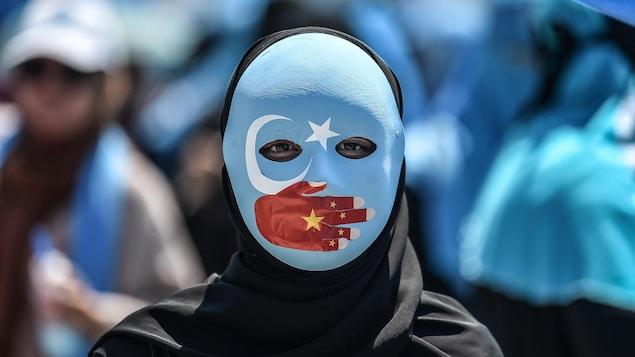 Un manifestant porte un masque à l'effigie du drapeau du Turkestan oriental. Une main représentant le drapeau chinois est peinte et couvre sa bouche. On ne voit que les yeux.