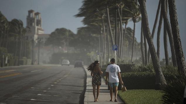 Un couple marche sur un trottoir sous un fort vent.