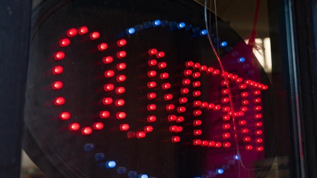 Un écriteau affichant ouvert à l'entrée d'une boutique.