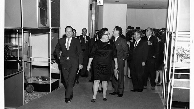 Photo en noir et blanc illustrant une foule souriante qui déambule dans un musée