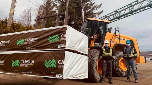 Des ouvriers du Groupe Lebel à l'usine de Dégelis, devant une charge de bois d'oeuvre sur un tracteur.