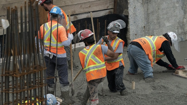 Des ouvriers coulent du béton sur un chantier.