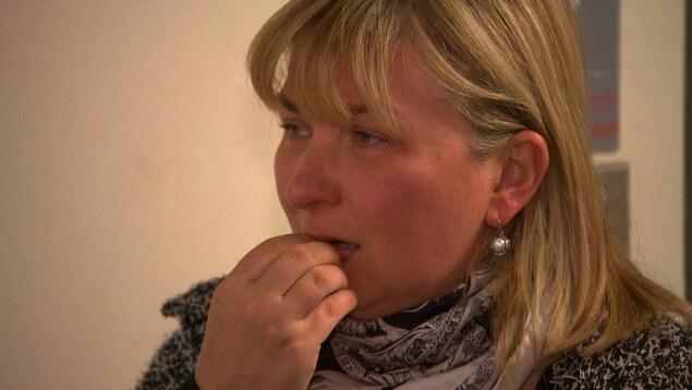 Oxana Berent a les yeux embués et porte la main à son visage.
