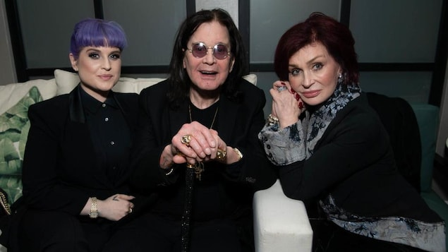 Les trois posent assis sur un sofa.