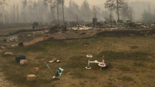 Une terre brûlée par le feu, un vélo et une maison qui a vraisemblablement brûlé sous un ciel couvert de fumée.