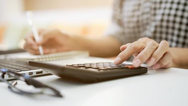Gros plan sur la main d'une femme qui appuie sur une touche d'une calculatrice en faisant son budget.