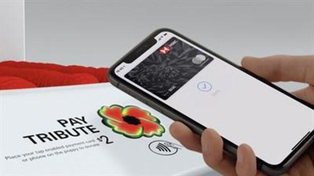 Un téléphone intelligent est dans la main d'une personne devant un système de paiement sans contact.