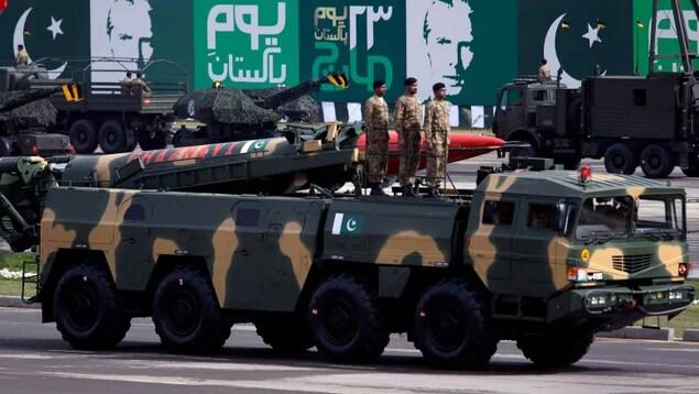 Un camion aux couleurs de camouflage avec des militaires et un missile sur le dessus.