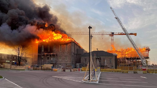 Toute la toiture d'un bâtiment en rénovation est en flammes.