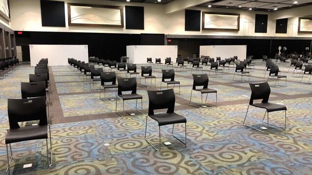 Des centaines de chaises sont alignées dans une vaste salle de conférence.
