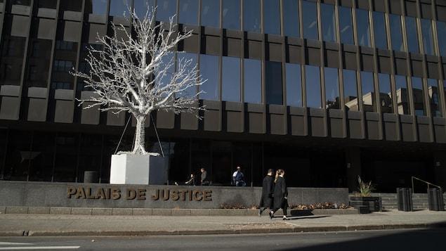Deux avocats marchent devant le palais de justice de Montréal.