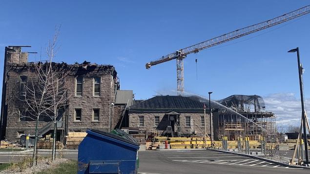Un édifice ravagé par les flammes se dresse sous un ciel bleu.