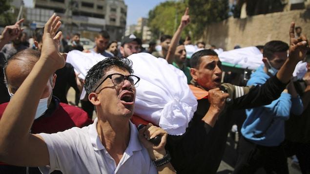 Des hommes pleurent et crient en transportant des corps enveloppés dans du tissu.