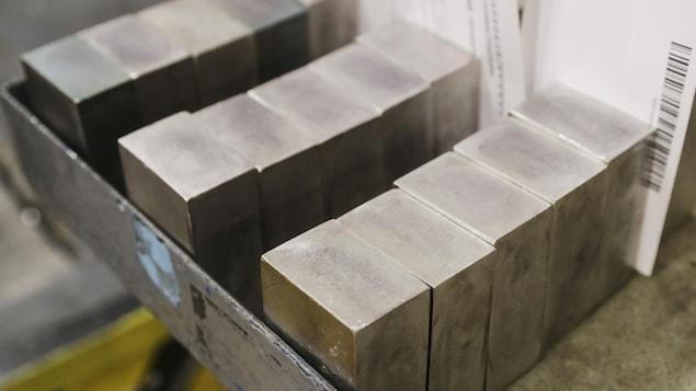 Des blocs d'un métal précieux dans une caisse.