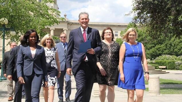 Un très grand homme, Brian Pallister, marche en souriant entouré de femmes, derrière le palais législatif du Manitoba.