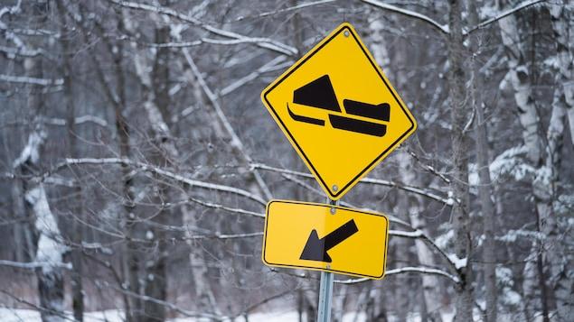 Une pancarte indiquant la présence d'un sentier de motoneige dans un secteur boisé de la Mauricie en hiver.