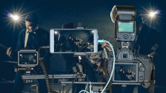 Un groupe de musique joue alors que deux caméras et un téléphone filment la scène.