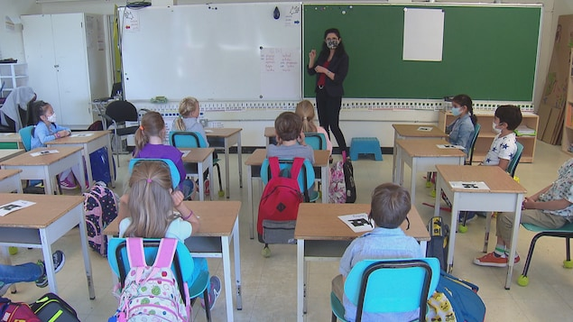 Une femme avec un masque parle aux élèves dans une salle de classe. Certains enfants portent un masque.