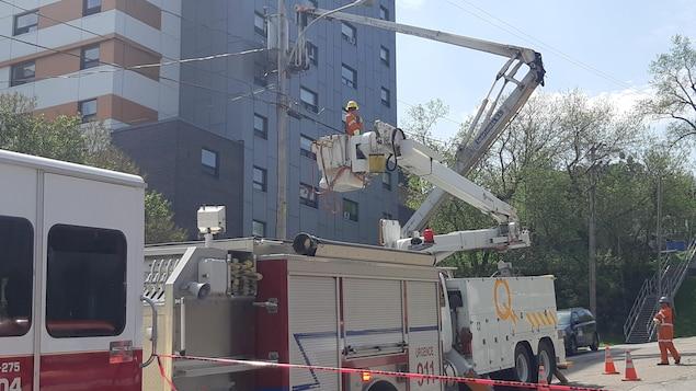 Un camion de pompiers et un camion d'Hydro-Québec avec une nacelle sont près d'un poteau électrique.