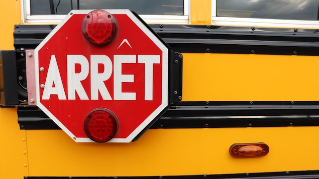 Un panneau d'arrêt avec deux feux clignotants rouge sur le côté d'un autobus scolaire.
