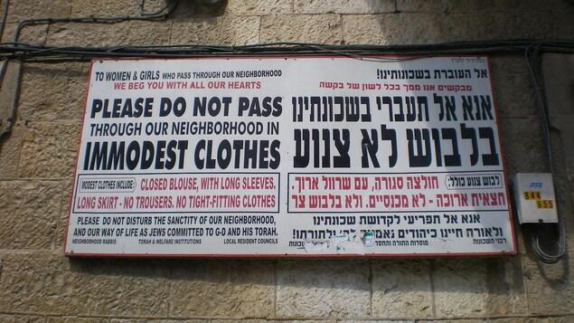 Deux affiches, une en hébreu, l'autre en anglais, sur un mur de Jérusalem.